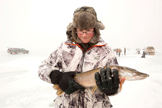 Travis Patterson holds the northern pike he caught while ice fishing last winter.