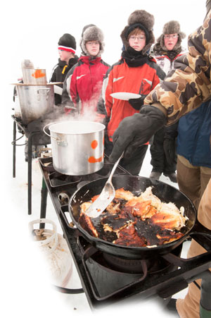 The Scouts line up to sample the fried northern pike fish fillets.