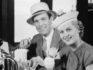 Man and woman in fancy hat drinking ice cream soda (B&W), portrait