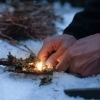 Man lighting a fire in a dark winter forest