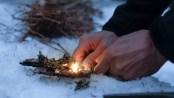 Man lighting a fire in a dark winter forest